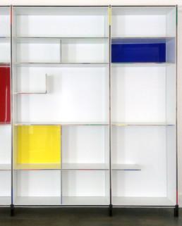 Bibliothèque en bois laqué blanc, façade de plastique de couleur, et sertissage en laiton doré