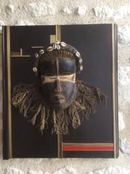 Masque africain, présentoir mural en bois, habillé de barrettes laiton, incrustation de plastique rouge